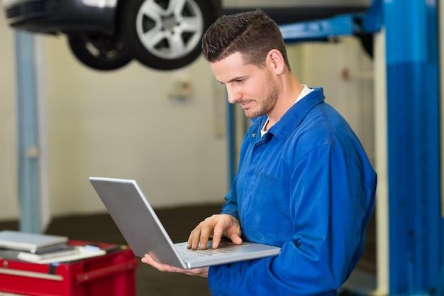 Mécanicien utilisant un ordinateur portable pour travailler au garage de réparation