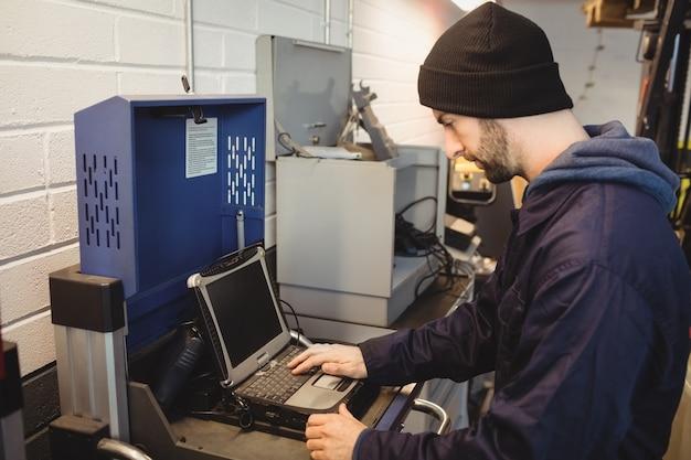 Mécanicien utilisant un ordinateur portable