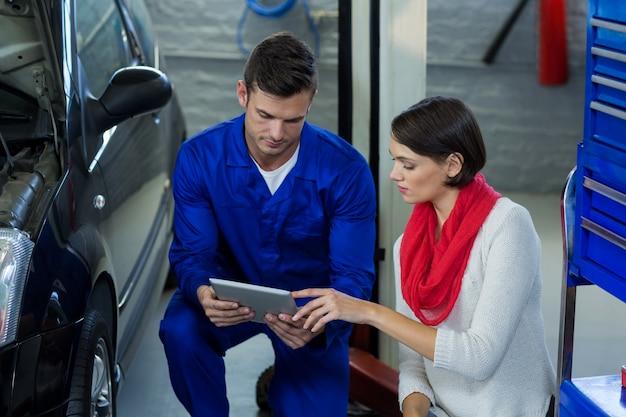 Mécanicien utilisant tablette numérique avec le client