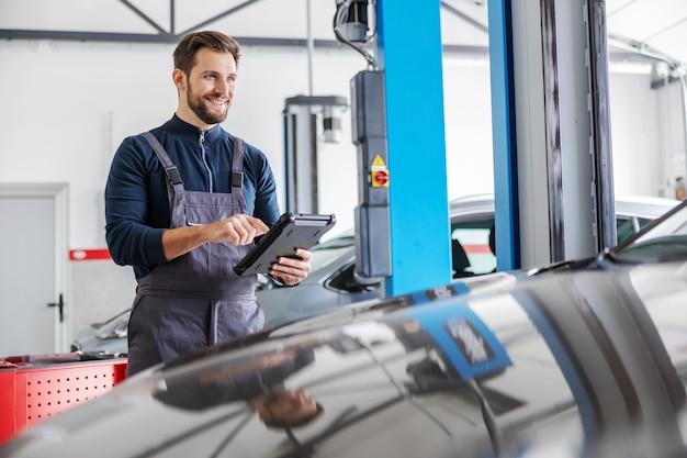 Mécanicien utilisant une tablette pour diagnostiquer un problème de voiture. garage d'intérieur de salon de voiture.
