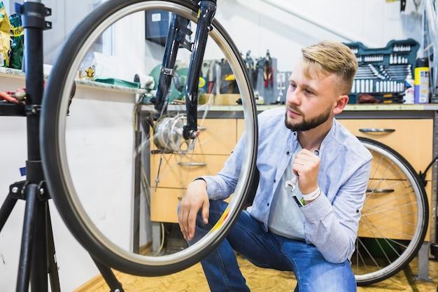 Mécanicien de vélo avec une clé en regardant le pneu de bicyclette