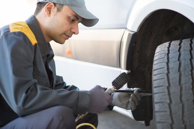 Mécanicien vérifiant la pression d'un pneu de camionnette