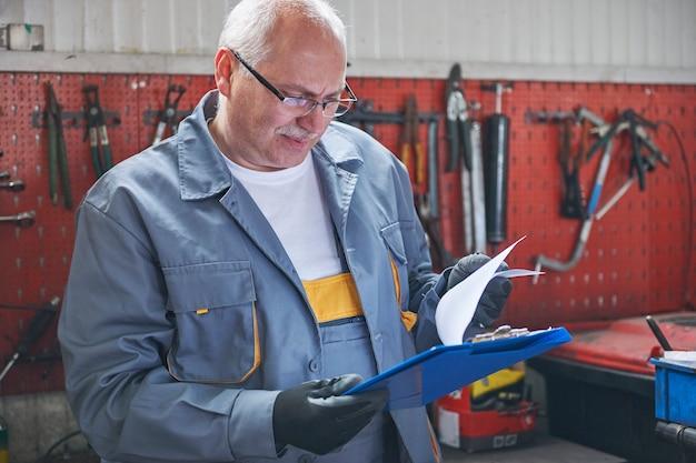 Mécanicien vérifiant un rapport de voiture