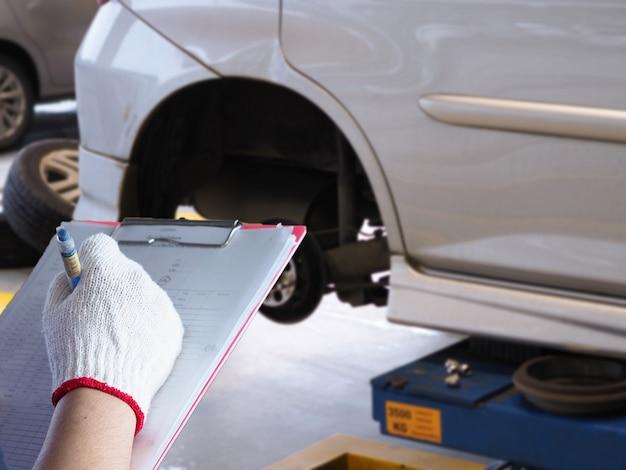 Le mécanicien vérifie la voiture.