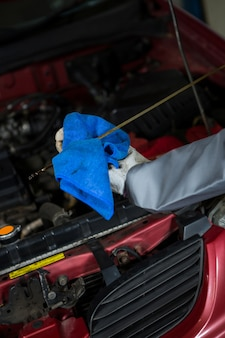 Mécanicien de vérifier le niveau d'huile dans un moteur de voiture