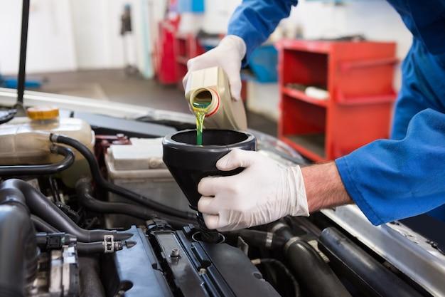 Mécanicien versant de l'huile dans une voiture