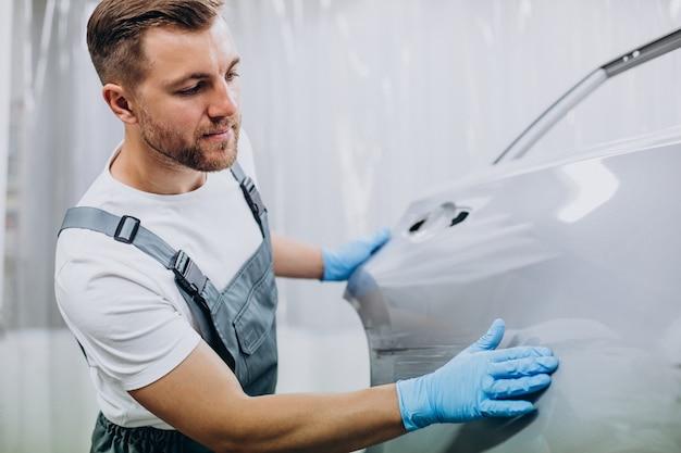 Mécanicien de voiture préparant l'aile de voiture avant de la peindre