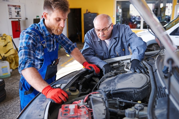 Mécaniciens réparant une voiture dans l'atelier