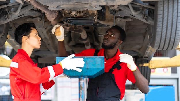 Mécaniciens stagiaires noirs masculins et féminins travaillant sous la voiture ensemble entretien de voiture et garage de service automobile.