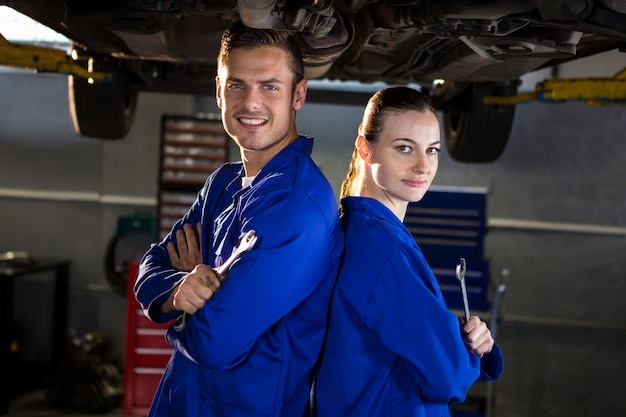 Mécanique debout dos à dos sous une voiture