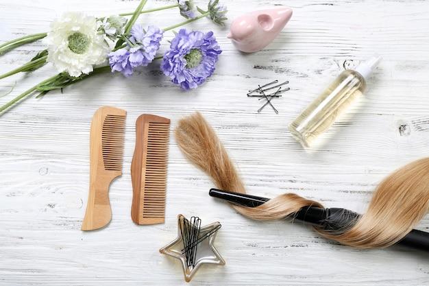 Mèche de cheveux avec des fleurs, du matériel de coiffure et des outils sur fond de bois clair