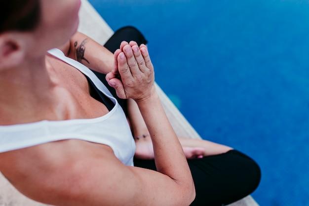 Méconnaissable jeune femme (fitness, yoga, corps en bonne santé) à la piscine