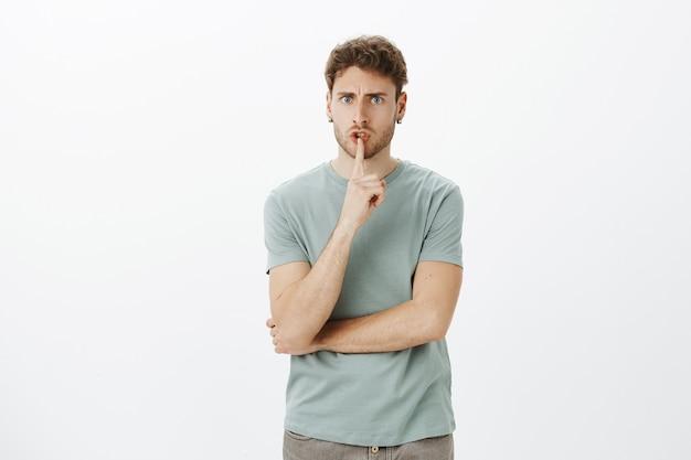 Mécontent de bel employeur sérieux en t-shirt décontracté, fronçant les sourcils et disant chut, exigeant le silence