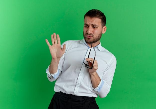 Mécontent bel homme tient des lunettes optiques à côté isolé sur mur vert