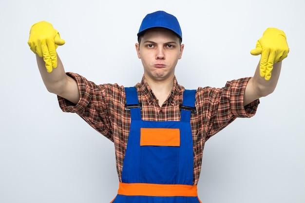 Mécontent de faire semblant de tenir quelque chose de jeune homme de ménage portant un uniforme et une casquette avec des gants