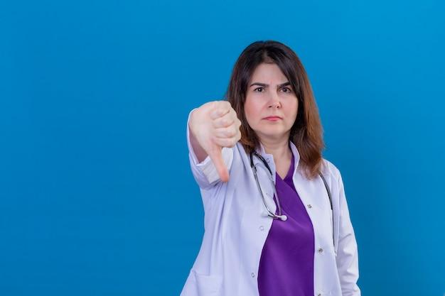 Mécontent femme médecin d'âge moyen portant un blouse blanche et avec un stéthoscope avec visage fronçant les sourcils montrant le pouce vers le bas debout sur l'espace bleu