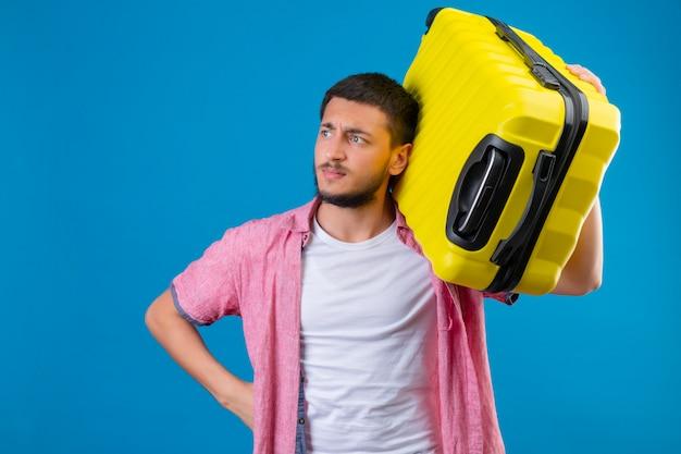 Mécontent jeune beau voyageur guy holding valise à côté avec froncement de sourcils debout sur fond bleu