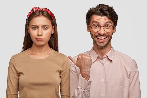 Mécontent jeune couple posant contre le mur blanc