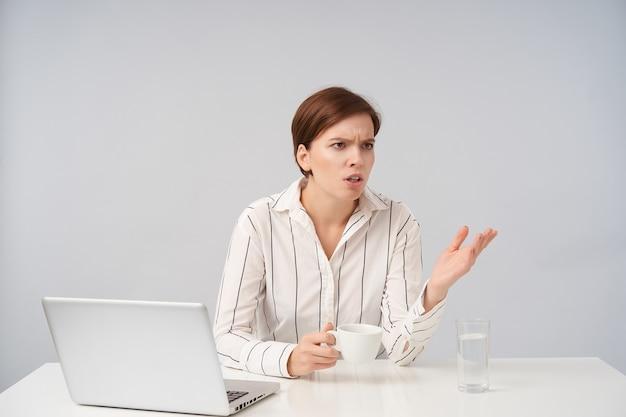 Mécontent jeune femme brune aux cheveux courts avec une coiffure décontractée fronçant les sourcils tout en regardant de côté avec la paume rasée, tenant une tasse en céramique tout en posant sur blanc
