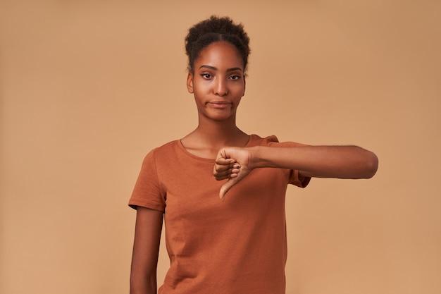 Mécontent jeune femme brune bouclée aux yeux bruns avec la peau foncée en gardant la main levée tout en faisant le pouce vers le bas avec la moue, debout sur beige