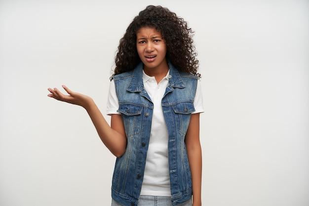 Mécontent jeune femme frisée aux cheveux noirs avec la peau foncée faisant la moue et fronçant les sourcils avec la main levée en se tenant debout sur blanc, vêtu de vêtements décontractés