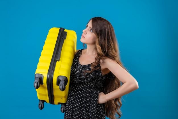 Mécontent jeune fille belle voyageur en robe à pois tenant valise à côté avec fronçant les sourcils debout sur l'espace bleu