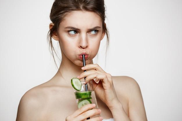 Mécontent jeune fille de l'eau potable avec des tranches de concombre sur fond blanc. cosmétologie de beauté et spa. traitement facial.
