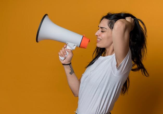 Mécontent jeune fille de race blanche brune se tient sur le côté et soulève les cheveux tenant haut-parleur isolé sur mur orange