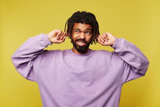 Mécontent jeune homme barbu brune à la peau sombre avec des dreadlocks fronçant les sourcils tout en regardant confusément vers le haut et en insérant l'index dans ses oreilles, isolé sur fond jaune