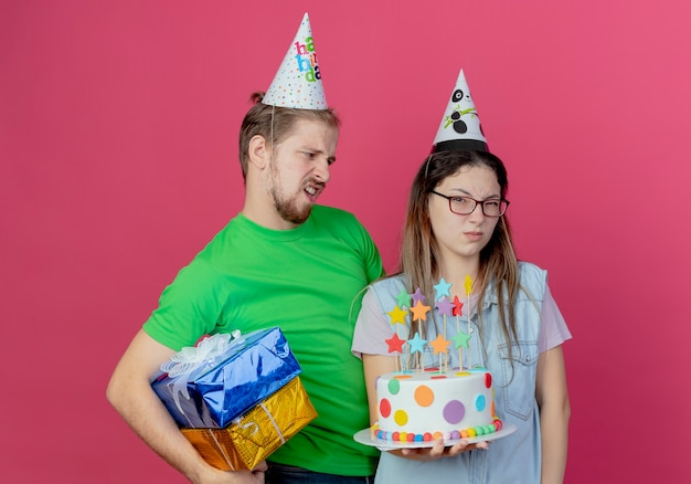 Mécontent jeune homme portant chapeau de fête détient des coffrets cadeaux à la jeune fille ennuyée portant chapeau de fête et tenant le gâteau d'anniversaire isolé sur mur rose