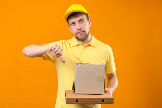 Mécontent jeune livreur en polo jaune et casquette tenant une boîte en carton montrant le pouce vers le bas debout sur orange isolé