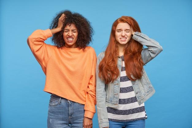 Mécontent de jeunes belles dames gardant les yeux tout en grimaçant des visages, en levant la paume vers la tête tout en se tenant sur un mur bleu, vêtus de vêtements décontractés
