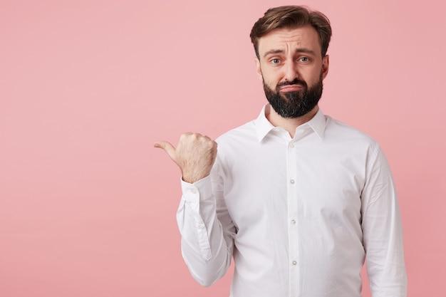 Mécontent joli jeune homme barbu aux cheveux bruns courts vêtus de vêtements formels tout en posant sur un mur rose, fronçant les sourcils avec les lèvres pliées et pointant avec le pouce de côté
