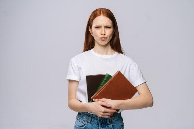 Mécontent, triste, jeune femme, étudiant universitaire, tenue, livre, et, regarder appareil-photo, sur, gris, fond