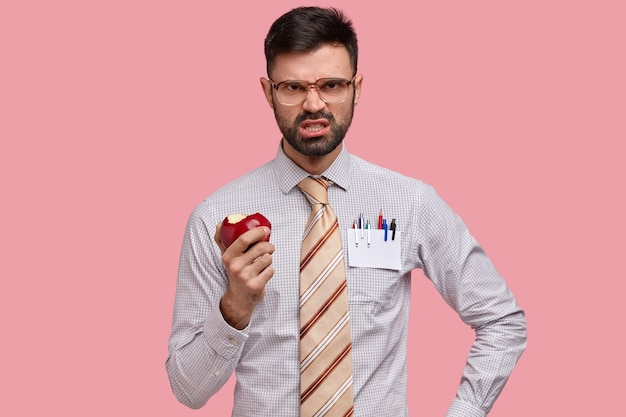 Le mécontentement ennuyé homme barbu fronce les sourcils, serre les dents avec colère, mange une pomme juteuse, n'aime pas l'idée de quelqu'un, habillé en formawear
