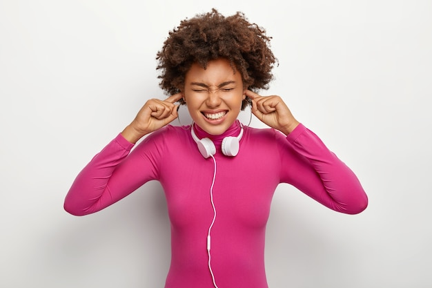Le mécontentement femme afro aux cheveux bouclés, se branche les doigts dans les trous d'oreille, ignore les bruits désagréables