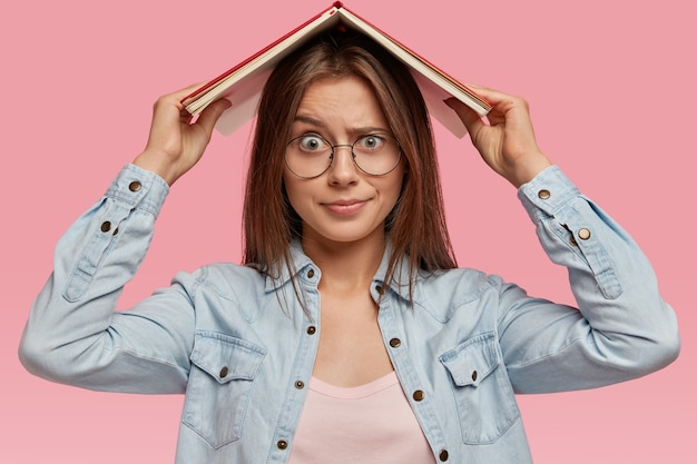 Le mécontentement femme aux cheveux noirs regarde avec une expression insatisfaite, se sent fatigué de l'apprentissage constant, garde le livre au-dessus de la tête, porte une chemise en jean, des lunettes optiques, exige des vacances, isolé sur un mur rose