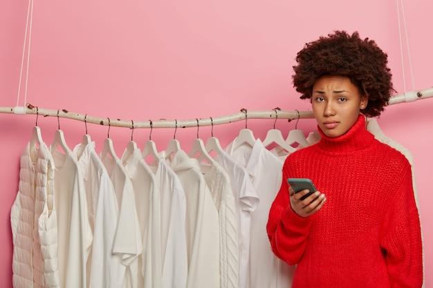 Mécontentement femme triste avec une coiffure afro tient un téléphone portable, se tient près de la garde-robe de la maison, pose avec le téléphone dans les mains, contrariée de ne pas avoir de tenue à la mode.