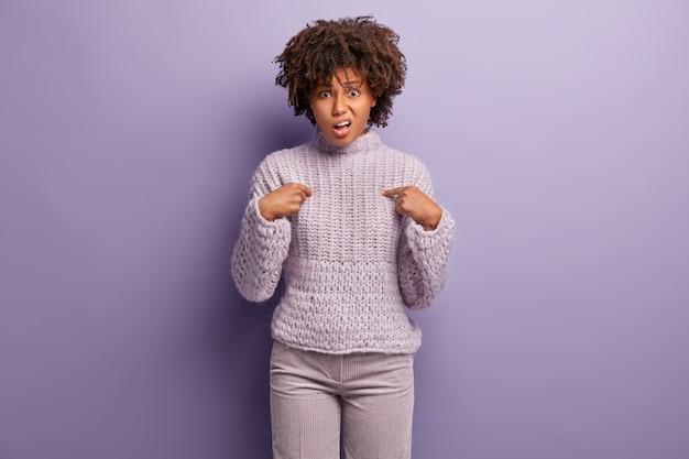 Le mécontentement indigné de la jeune femme se pointe du doigt, demande pourquoi c'est son devoir, fronce les sourcils avec mécontentement, exprime son désaccord, porte un pull en tricot, isolé sur un mur violet. pourquoi moi?