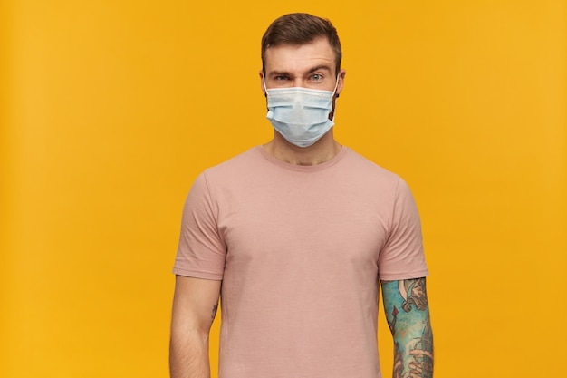 Mécontentement, mec curieux aux cheveux bruns. porter un t-shirt rose et un masque médical de protection. a un tatouage. lève le sourcil et isolé sur un mur jaune