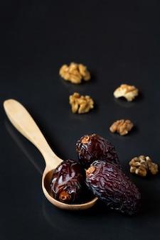 Med jool dates fruits dans une cuillère en bois et noix sur fond noir