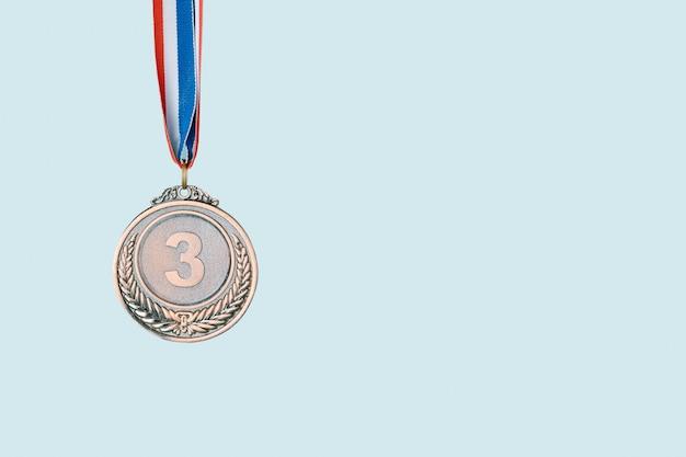 Médaille de bronze sur fond bleu. award et victoire concept.copy space