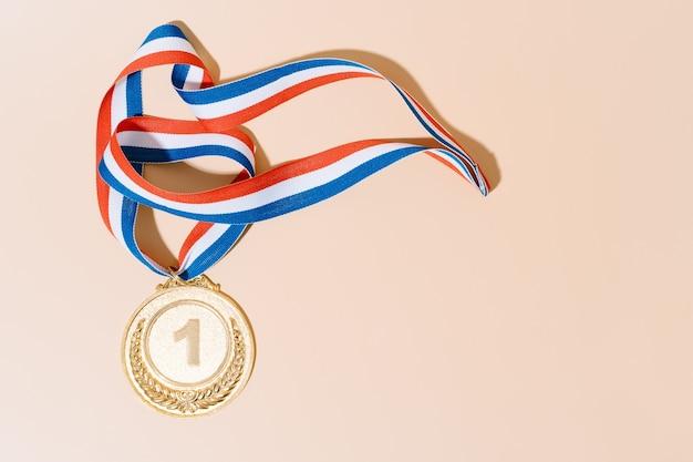 Médaille d'or sur fond pastel.award et victoire concept.copy space