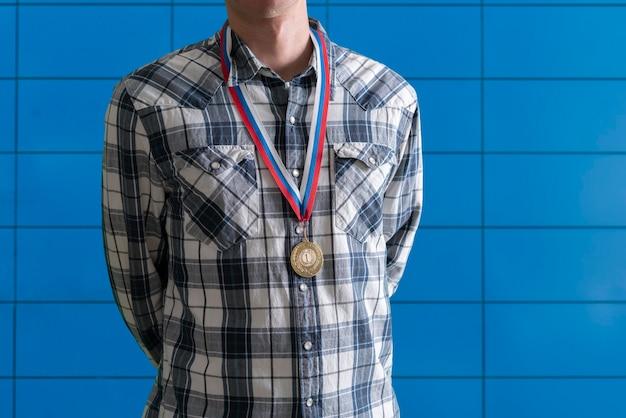 Une médaille d'or sur la poitrine humaine réalise le succès