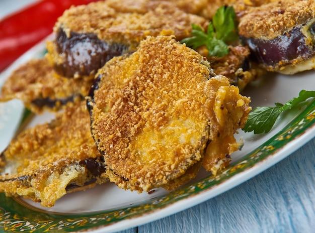 Médaillons d'aubergines, il suffit de draguer des tranches d'aubergines trempées dans des œufs dans une savoureuse combinaison de parmesan, de miettes et d'assaisonnements