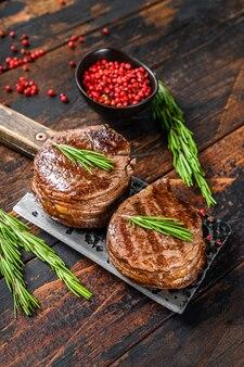 Médaillons steaks du filet de bœuf. surface en bois sombre. vue de dessus.