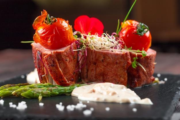 Médaillons de veau aux asperges sur vaisselle noire, table en bois