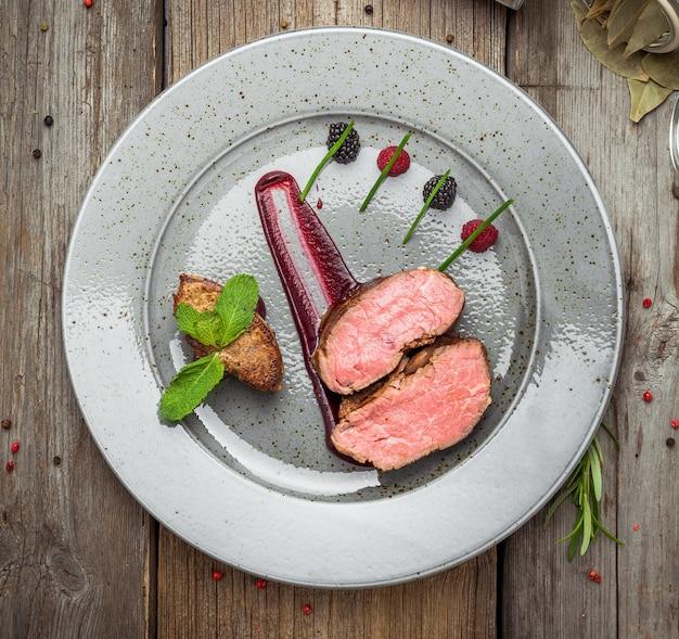 Médaillons de veau, sauce sur une assiette surface en bois