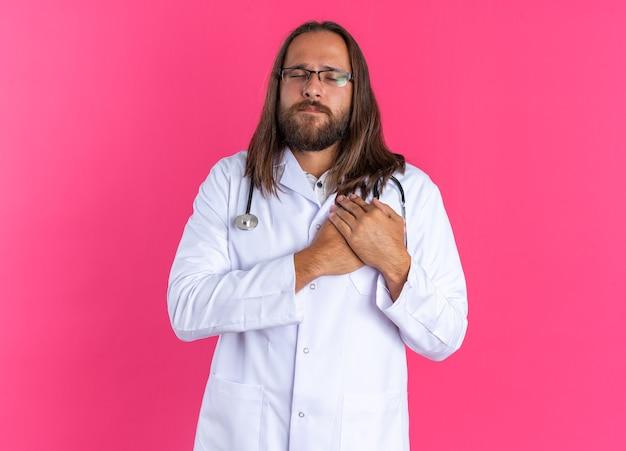 Un médecin adulte reconnaissant portant une robe médicale et un stéthoscope avec des lunettes faisant un geste de remerciement à dieu avec les yeux fermés isolés sur un mur rose