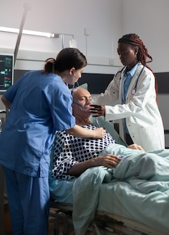 Un médecin africain aide un patient âgé à respirer à l'aide d'un tube de ventilation respiratoire dans une chambre d'hôpi...